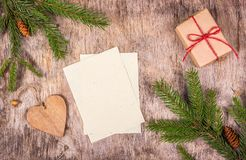 Empty sheets on wooden background. Christmas decorations with gift and fir tree. Preparing for Christmas, list of gifts. royalty free stock photography
