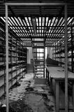 Empty shelves in storage room. Rows of empty shelves in abandoned factory storage room. Black and white Royalty Free Stock Photo