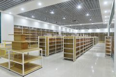 Empty shelves of supermarket interior. Empty store interior,Led lamps are installed on shop square shape ceiling ,empty shelves Royalty Free Stock Images