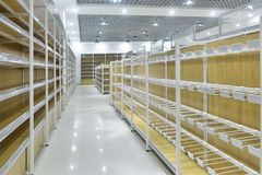Empty shelves of supermarket interior. Empty store interior,Led lamps are installed on shop square shape ceiling ,empty shelves Stock Image