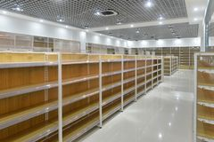 Empty shelves of supermarket interior. Empty store interior,Led lamps are installed on shop square shape ceiling ,empty shelves Stock Photo