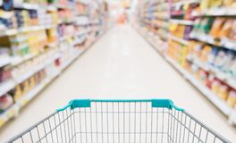 Empty shopping cart with abstract blur supermarket. Discount store aisle and product shelves interior defocused background Stock Photo