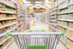 Empty shopping cart with abstract blur supermarket. Discount store aisle and product shelves interior defocused background Stock Images