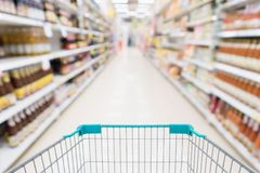 Empty shopping cart with abstract blur supermarket. Discount store aisle and sauce product shelves interior defocused background Royalty Free Stock Images