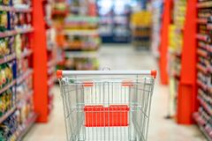 Empty shopping cart with blur supermarket  store aisle and product shelves interior background. Empty shopping cart with blur supermarket  store aisle and stock image