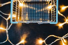 Empty shopping cart on concrete desk surrounded by fairy lights stock photos