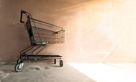 Empty shopping cart on the concrete wall. Empty shopping cart on the concrete wall in the morning Stock Photography