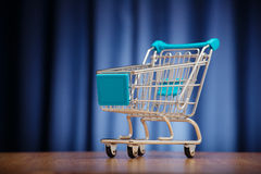 Empty shopping cart on dark blue background. Royalty Free Stock Image