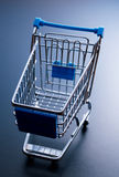 Empty shopping cart on dark blue background. Stock Photography