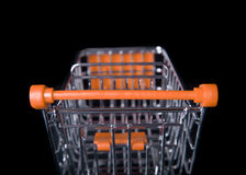 Empty Shopping Cart isolated in black. Empty Orange Shopping Cart isolated in black from behind Royalty Free Stock Image