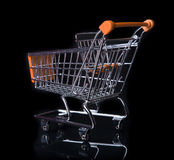Empty Shopping Cart isolated in black. Empty Orange Shopping Cart isolated in black from behind Royalty Free Stock Photos