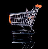 Empty Shopping Cart isolated in black. Empty Orange Shopping Cart isolated in black from side view Stock Photo