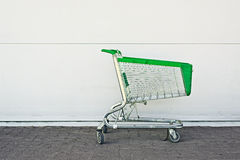 Empty Shopping Cart. Parked in front of large supermarket. Consumerism concept Royalty Free Stock Image