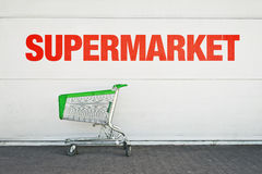 Empty Shopping Cart. Parked in front of large supermarket. Consumerism concept Royalty Free Stock Images