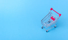Empty shopping cart. With the red handle on a blue background Royalty Free Stock Photos