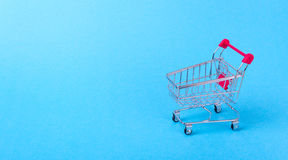 Empty shopping cart. With the red handle on a blue background Royalty Free Stock Photography