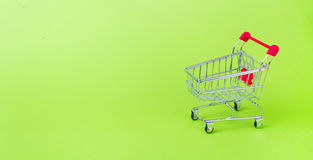 Empty shopping cart. With the red handle on a green background Stock Photos