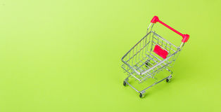 Empty shopping cart. With the red handle on a green background Royalty Free Stock Images
