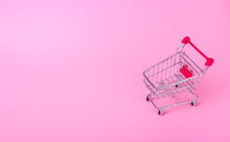Empty shopping cart. With the red handle on a pink background Royalty Free Stock Photo