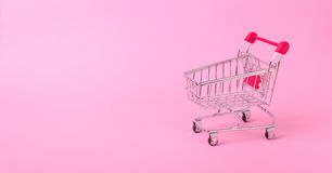 Empty shopping cart. With the red handle on a pink background Royalty Free Stock Photos