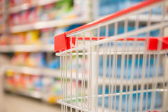 Empty shopping cart in supermarket. Empty shopping cart in a supermarket Stock Photo