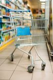 Empty shopping cart in supermarket. Close up view of empty shopping cart in supermarket Stock Photos