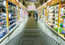 Empty shopping cart in supermarket store interior Stock Photos