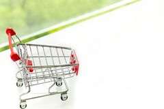 Empty shopping cart trolley on white table with green background. S Royalty Free Stock Images