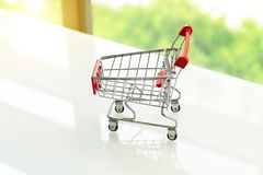 Empty shopping cart trolley on white table with green background. S Stock Photos