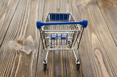 Empty shopping cart on wooden background.  Royalty Free Stock Photos