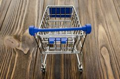 Empty shopping cart on wooden background.  Stock Image