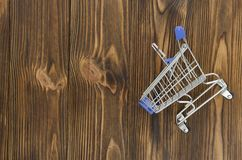 Empty shopping cart on wooden background.  Stock Photography