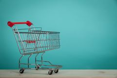 Empty shopping cart on wooden table with green backround. Consumerism concept. Online shopping concept. Empty shopping cart on wooden table with green backround Royalty Free Stock Photo