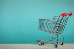 Empty shopping cart on wooden table with green backround. Consumerism concept. Online shopping concept. Royalty Free Stock Images