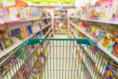 Empty shopping trolley cart in bookshelf  book store Stock Photos