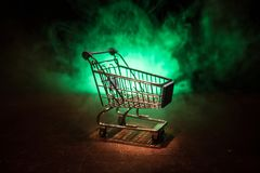 Shopping trolley on dark toned foggy background with some copy space. Empty shopping trolley on dark toned foggy background with some copy space. Financial Royalty Free Stock Photography