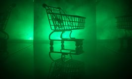 Shopping trolley on dark toned foggy background with some copy space. Empty shopping trolley on dark toned foggy background with some copy space. Financial Stock Photos