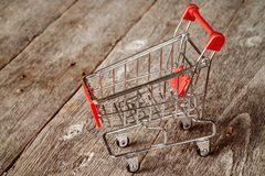 Empty shopping trolley. On the wooden background Royalty Free Stock Photos