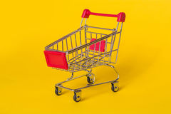 Empty shopping trolley on a yellow background. Shop basket for products. Royalty Free Stock Photos
