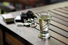 Empty shot glass on table with matches and keys in the background Stock Images
