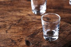 Empty shot glass for vodka, tequila or moonshine, copy space, selective focus. Empty shot glass for vodka, tequila or moonshine, copy space, selective  focus stock photos
