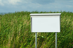 Empty sign. White and empty sign with high grass in the background Royalty Free Stock Photo