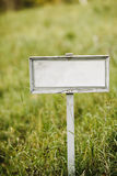 Empty signboard on a green field Royalty Free Stock Image