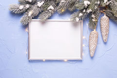 Empty silver frame, Christmas decorations and fairy light on blu Stock Photography