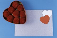 Empty silver letter with two hearts of red and white color box next to balls of cotton red on a blue background stock photos