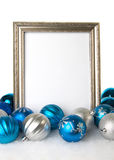 An empty Silver Picture Frame with Blue and Silver Christmas Ornaments. A vertical silver picture frame on a white background with blue and silver Christmas stock photo