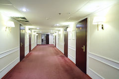 Empty simple light hallway with many wooden doors. To hotel rooms Stock Photography