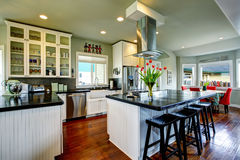 Empty simple old kitchen with hardwood floor and white cabinets. Black counter top in American historical house. Connected to dining area Stock Photo