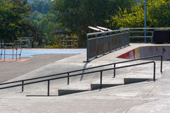 Empty skatepark at noon with ramps and grind rails. Empty skatepark at noon with ramps, grind rails, half pipe and fitness equipment Royalty Free Stock Image