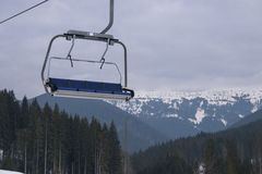 Empty ski chairlift with beautiful mountains forest on the background. Empty four seats ski snowboard chairlift lift at ski resort with beautiful mountains and Royalty Free Stock Images